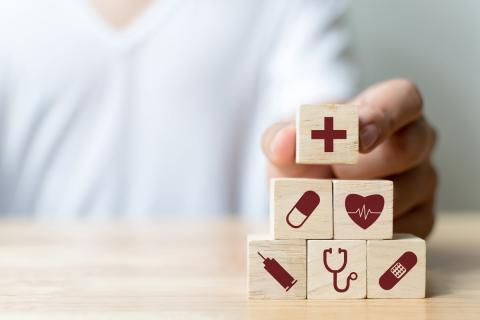 A man stacks blocks with healthcare and medical symbols printed on them.